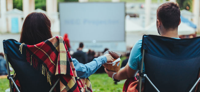 A woman and man eating snacks while watching a movie outdoors